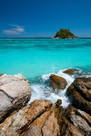 A small island is seen in a beautiful turquoise ocean off a rocky coastline.