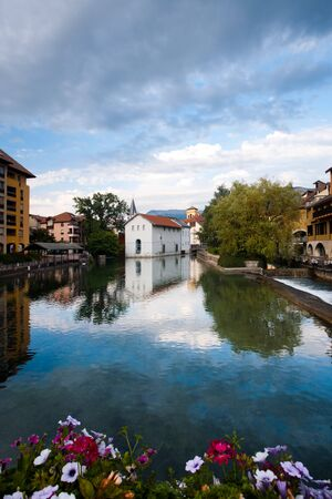 A wide canal beautifully reflects the historic city center of Annecy, a French village in the Alps.