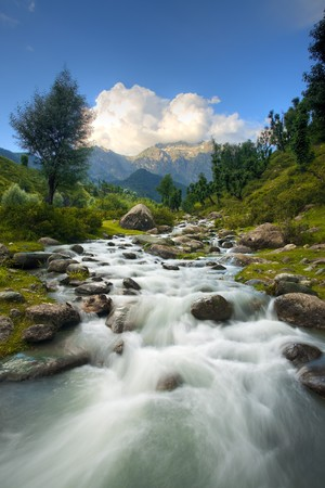 A beautiful river and Himalayan mountain background in Kashmirs Aru Valley in vertical landscape.