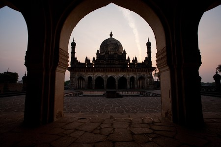 mughal: Ibrahim Rauza, a Mughal mausoleum, is framed by a neighboring arch at sunrise.