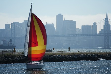 The skyline of San Francisco and the Bay Bridge provide a scenic background for leisurely sailing around the bay. Banque d'images