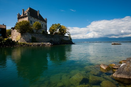 Yvoires fortified castle is wonderfully reflected in the crystal clear waters of Lake Geneva
