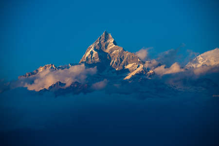 Clouds gather around the peak of Machapuchre mountain in the Annapurna range of the Himalayas in Nepal.