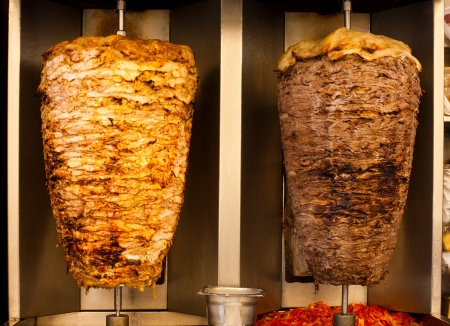 Delicious slabs of skewered fast food shawerma chicken and lamb meat turn on a spit