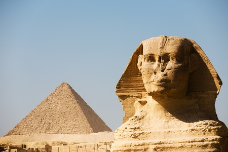 A closeup of the head of the Great Sphinx and the Pyramid of Menkaure in the distance in Giza, Cairo, Egypt photo