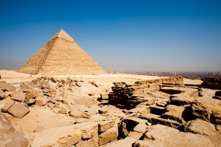 The funerary temple at the base of the Pyramid of Menkaure and the Pyramid of Khafre in the distance at the edge of the bustling city of Cairo, Egypt photo