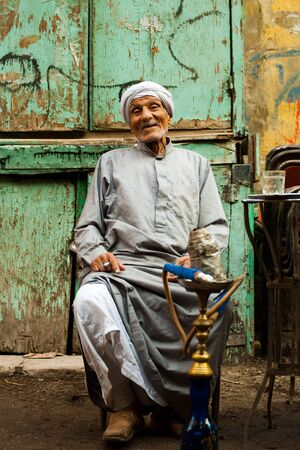 cairo: CAIRO - OCTOBER 11: A friendly old Egyptian man sits at a street cafe smoking sheesha in Islamic Cairo October 11, 2010 at Cairo, Egypt