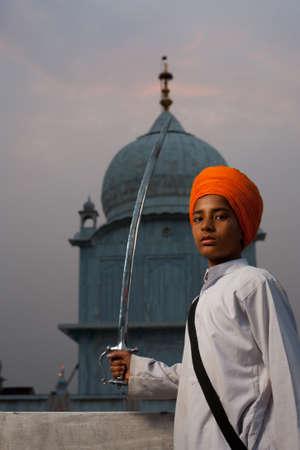 gurudwara: PAONTA SAHIB - MAY 22: A young Sikh boy brandishing a sword at the Paonta Sahib Gurudwara, famous for its past warriors May 22, 2009 in Paonta Sahib, Himachal Pradesh, India Editorial