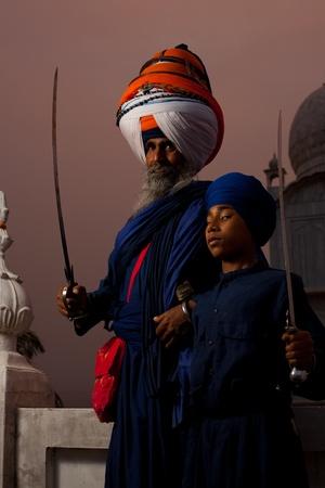 gurudwara: PAONTA SAHIB - MAY 22: The large turbaned gurudwara leader and a young student brandish swords at the Paonta Sahib Gurudwara, famous for its past warriors May 22, 2009 in Paonta Sahib, Himachal Pradesh, India