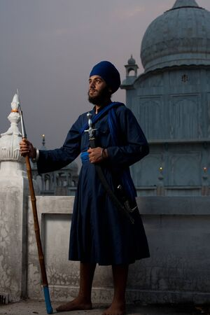 gurudwara: PAONTA SAHIB - MAY 22: A young Sikh man brandishing a sword and spear at the Paonta Sahib Gurudwara, famous for its past warriors May 22, 2009 in Paonta Sahib, Himachal Pradesh, India