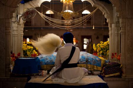Paonta Sahib - May 23: A Sikh man waves a fluffy wand at an ornately carved and decorated altar inside the Paonta Sahib gurudwara's prayer hall May 23, 2009 at Paonta Sahib, Himachal Pradesh, India Éditoriale