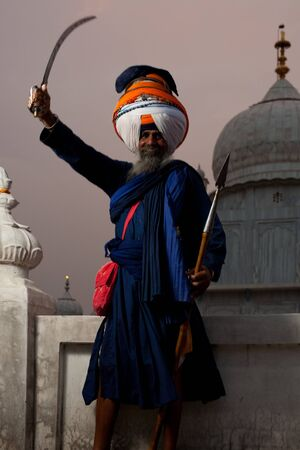 gurudwara: Paonta Sahib - May 22:  The elder head of the Paonta Sahib Gurudwara smiles while raising his sword in victory May 22, 2009 at Paonta Sahib, Himachal Pradesh, India