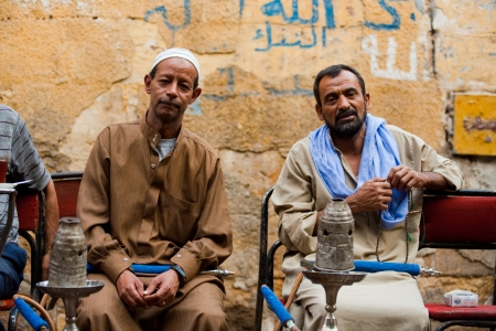 CAIRO - OCTOBER 11: A pair of Egyptian men enjoy smoking shisha at a traditional streetside ahwa (cafe) in Islamic Cairo October 11, 2010 at Cairo, Egypt Editoriali