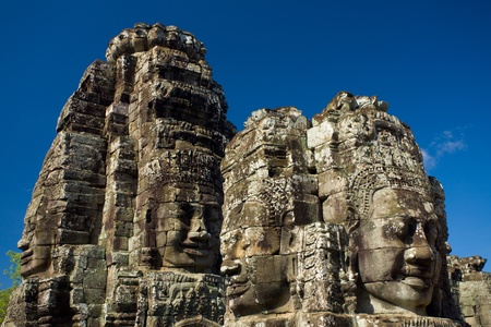 The happy faces of the Bayon temple at eye-level against a beautiful blue sky at the Angkor Wat temple complex in Siem Reap, Cambodia Фото со стока