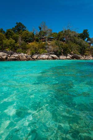 Jungle bungalows overlook the crystal clear ocean water on island paradise, Ko Lipe, Thailand