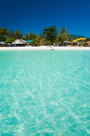 A truly white sand beach and crystal clear water resembling a swimming pool on the island paradise of Ko Lipe, Thailand