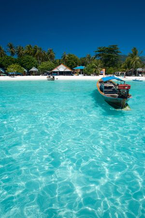 A traditional longtail boat floats in perfect crystal clear water on the island paradise of Ko Lipe, Thailand Stock Photo