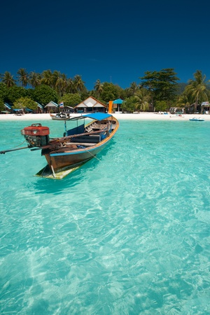 A closeup of a traditional Thai longtail boat floating in perfect crystal clear ocean on the island paradise of Ko Lipe, Thailand