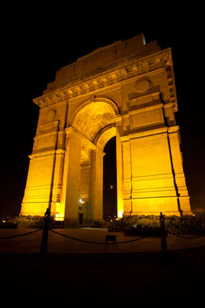 The moon is visible through the India Gate memorial beautifully illuminated at night in central Delhi, India Banque d'images