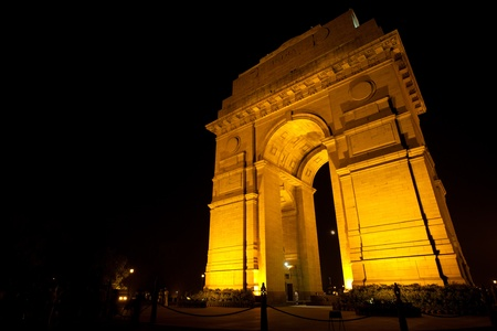 The moon is visible through Delhis India Gate memorial, tastefully illuminated by floodlights at night