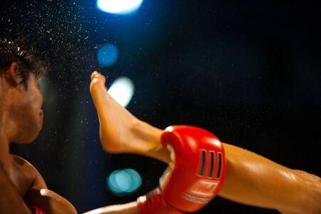 thai kick boxing: BANGKOK - OCTOBER 12: A kick catches the head of a muay thai boxer and sends sweat flying through the air at Fight Night October 12, 2010 at Bangkok, Thailand