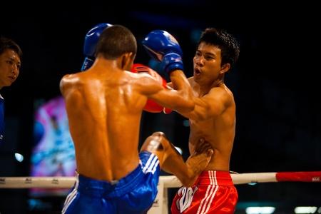 BANGKOK - OCTOBER 12:  A muay thai fighter receives a kick jab to the stomach at Fight Night October 12, 2010 at Bangkok, Thailand