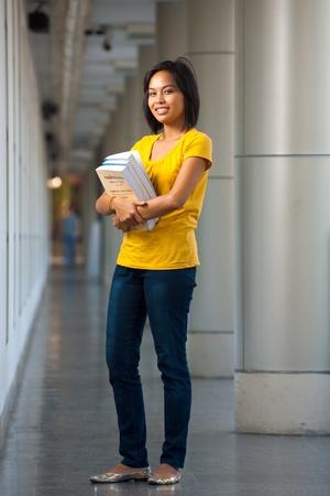 Portrait de pleine longueur d'un étudiant heureux et souriant transportant des livres. Jeune femme asiatique modèle thaïlandais fin d'adolescence, début des années 20 d'origine chinoise.