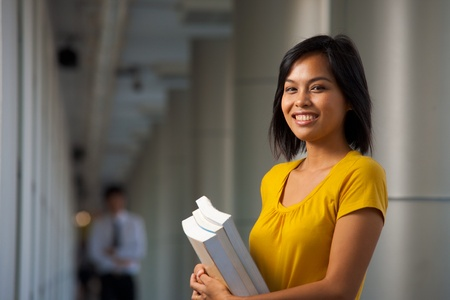 A half portrait of a cute smiling college student on a beautiful modern campus.  Young female Asian Thai model late teens, early 20s of Chinese descent. Stock Photo - 8479355