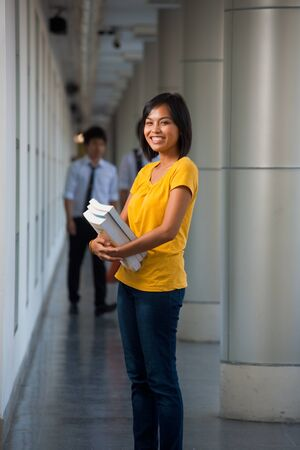 cradling: Three quarter length portrait of a cute laughing college student cradling books on a modern university campus.  Young female Asian Thai model late teens, early 20s of Chinese descent. Stock Photo