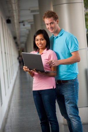 british man: A pair of happy college students look up from sharing a laptop on a university campus.   20s female Asian Thai model of Chinese descent.  20s tall male caucasian model British nationality.