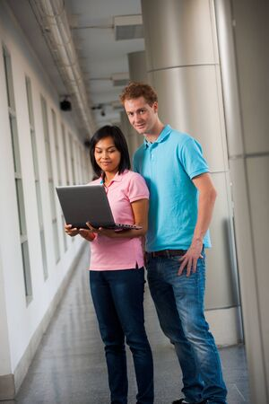 Two attractive college students share a laptop on a beautiful university campus.  20s female Asian Thai model of Chinese descent looking at screen.  20s tall male caucasian model British nationality looking at camera. photo