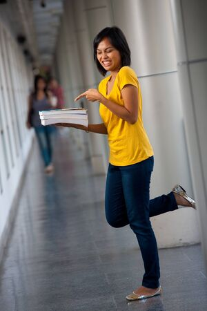 disgusted: An angry young college student points at her textbooks with a disgusted expression.  20s female Asian Thai model of Chinese descent. Stock Photo
