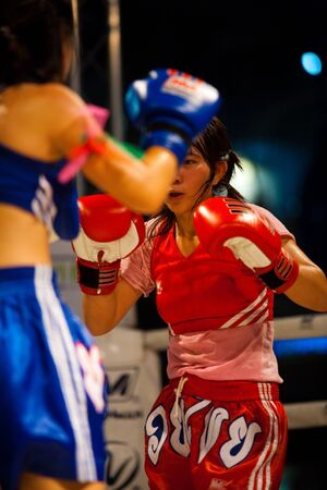 BANGKOK - OCTOBER 12: Two female muay thai kickboxers face off at Fight Night October 12, 2010 at Bangkok, Thailand