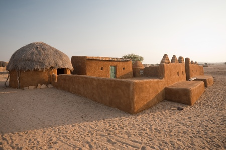 mud house: A traditional thatched roof mud hut and home in the Thar desert in Khuri, Rajasthan, India Stock Photo