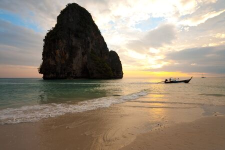 A longtail boat rides through the Andaman sea in front of a large limestone mountain during sunset at Railay Phra Nang beach, Thailand.