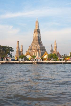 Wat Arun, the Temple of Dawn shines beautifully in the morning sun along the Chao Phraya river.