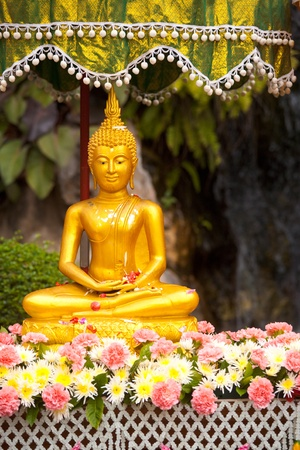 A shaded Buddha statue covered with flower petals after being cleansed and perfumed for Songkran, Thai New Year in Thailand