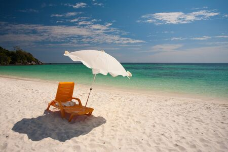Beach chairs and parasols on the perfect white sand beach lined by beautiful crystal clear water on paradise island Koh Lipe, Thailand.  (aka Ko Lipeh)