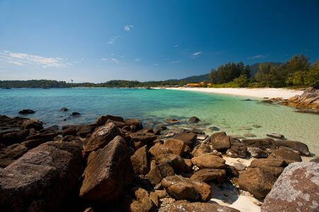 A rocky portion lines the perfect white sand beach and transparent clear waters of Koh Lipe, Thailand (aka Ko Lipeh).