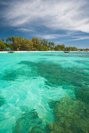 pristine coral reef: Sotto le cristalline color smeraldo acque turchesi sono grandi formazioni coralline barche tradizionali tailandesi scremare sopra l'acqua sull'isola di paradiso, Koh Lipe (aka Ko Lipeh), Thailandia