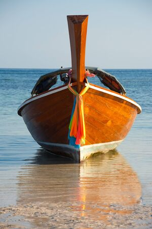 A grounded longtail boat and its reflection head on in low tide on the paradise island of Koh Lipe (Ko Lipeh) Thailand.