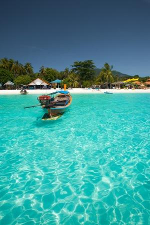 Un barco de pescadores tradicionales flota en agua azul Esmeralda cristalina perfecta en el paraíso de la isla de Koh hasta (aka Ko Lipeh), Tailandia