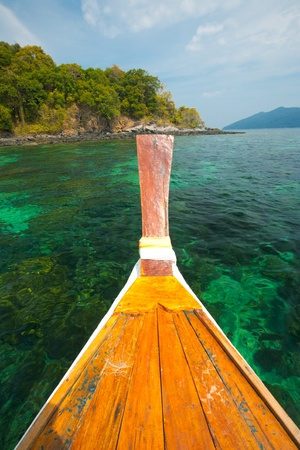 pristine corals: The bow of a traditional longtail boat overlooks the crystal clear water and coral reef in Tarutao national park, Thailand, an area known for great diving and snorkeling. Stock Photo