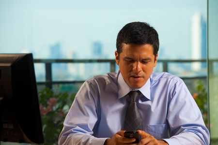 A hispanic businessman receives bad news by text (sms) on his smartphone.  30s latino American male of mixed Brazilian - Mexican descent. photo