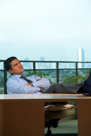 A successful hispanic executive takes a minute for a thought session while reclining at his desk.  30s latino American male of mixed Brazilian - Mexican descent. photo