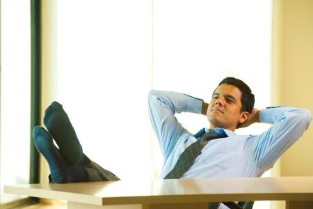 성공적인 히스패닉계 남성은 그의 머리 뒤에 손으로 그의 책상에서 휴식하고 이완시킵니다. 혼합 된 브라질 - 멕시코 출신의 30 대 라틴계 미국 남성. 스톡 콘텐츠