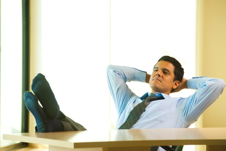 A successful hispanic male reclines and relaxes at his desk with hands behind his head.  30s latino American male of mixed Brazilian - Mexican descent.