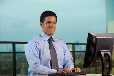 Successful hispanic office worker using a computer in an office with great view.   30s latino American male of mixed Brazilian - Mexican descent.