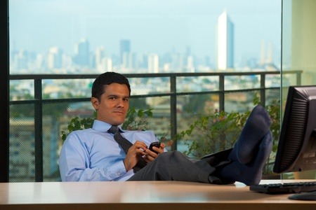 A handsome successful hispanic business executive reclines in his office chair with a great downtown city skyline view.  30s latino American male of mixed Brazilian - Mexican descent. photo