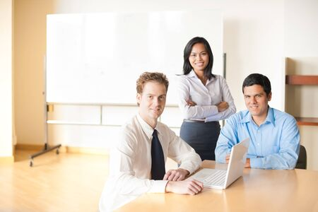 A caucasian businessman leads a team meeting with his hispanic and asian coworkers using a laptop Stock Photo - 9866992